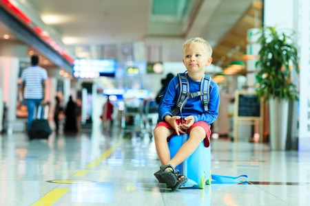 sit: cute little boy waiting in the airport, child travel Stock Photo