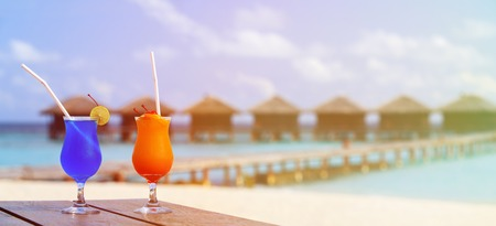 Two cocktails on luxury tropical beach resort, wide panorama