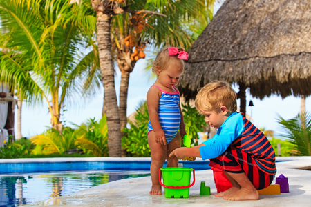 young boy in pool: little boy and toddler girl playing in swimming pool at beach