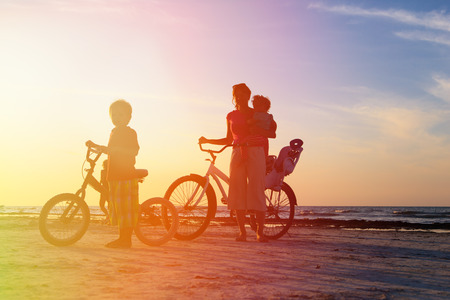leisure sports: silhouette of mother with kids biking at sunset Stock Photo