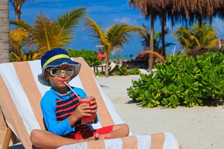 fruta tropical: jugo lindo beber muchacho en la playa tropical