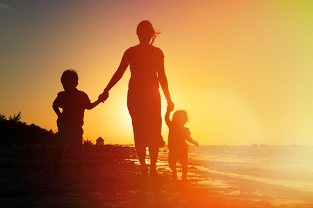 child protection: mother and two kids walking on sand beach at sunset