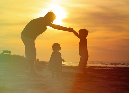 daugther: father and son making home for little daugther at sunset beach