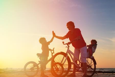 라이프 스타일: 자전거에 두 아이들과 자전거 타는 가족 실루엣, 아버지