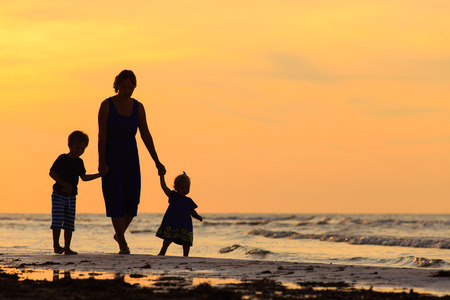 mother and two kids walking on sand beach at sunset