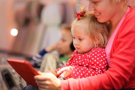 airplane girl: mother and little daughter looking at touch pad in plane, family travel