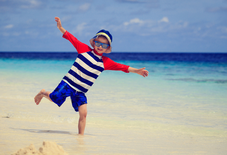 play: little boy having fun on tropical beach vacation