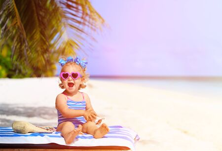 little girl swimsuit: cute little girl with seashells on summer tropical beach Stock Photo