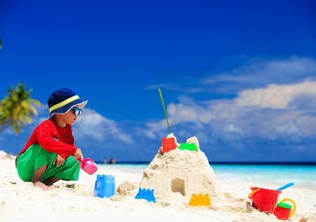 sandcastle: little boy building sandcastle on tropical beach Stock Photo
