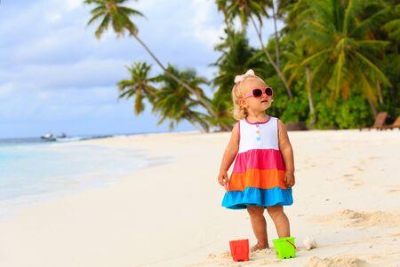 bebes niñas: muchacha linda del niño que juega con los juguetes en la playa tropical Foto de archivo