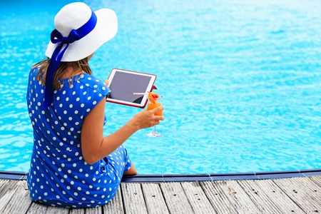 Young woman looking at touch pad with cocktail near swimming pool
