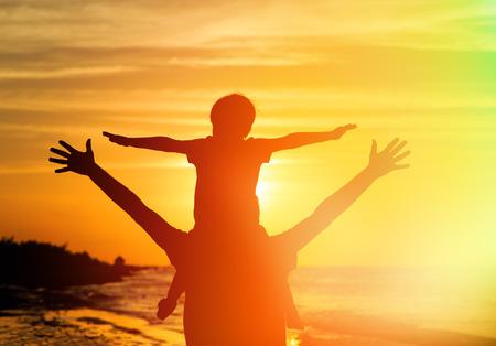 familias felices: padre e hijo se divierten en la playa de la puesta del sol