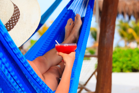 rest and relaxation: woman with cocktail relaxed in hammock on tropical beach