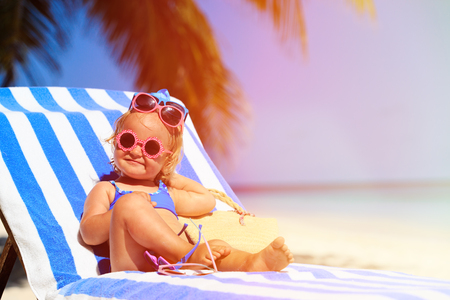 little girl beach: happy cute little girl trying on sunglasses at the beach