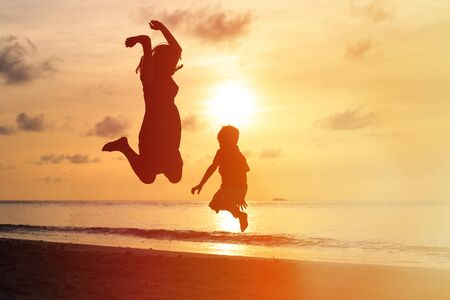 family outdoor: mother and son jumping at sunset beach, happy family