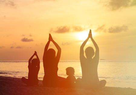 familie silhouetten die yoga doet bij zonsondergang op zee Stockfoto