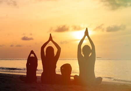 Familie Silhouetten, die Yoga am Sonnenuntergang Meer Standard-Bild - 43159925