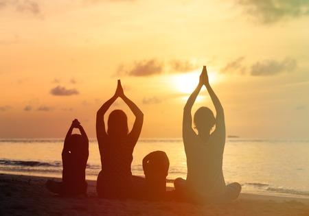 beach yoga: family silhouettes doing yoga at sunset sea