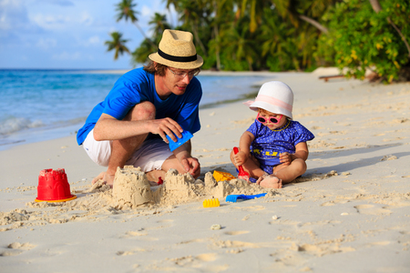 sandcastle: father and little daughter building sandcastle on summer beach Stock Photo