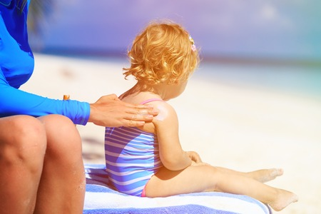 sun lotion: parent applying sunblock cream on daughter shoulder, sun protection