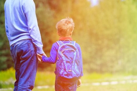 holding back: father holding hand of little son with backpack outdoors, back to school Stock Photo