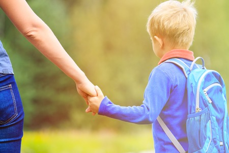 holding back: Mother holding hand of little son with backpack outdoors, back to school Stock Photo