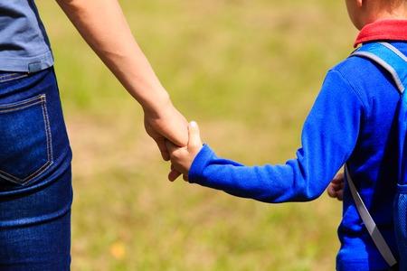 アウトドアのバックパックと幼い息子の手を握って、学校に戻っての母