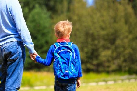 アウトドアのバックパックと幼い息子の手を握って、学校に戻っての父