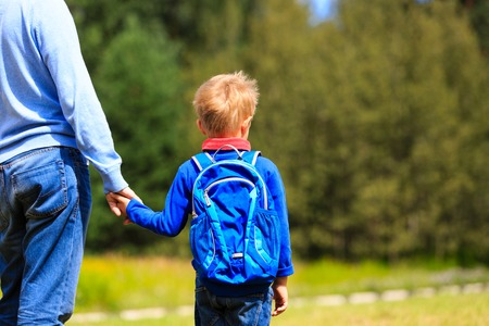father holding hand of little son with backpack outdoors, back to school Stock fotó