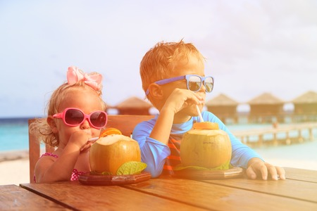 frutas divertidas: poco niño y niña niño pequeño cóctel de coco beber tropical en la playa, viajes de lujo niños Foto de archivo