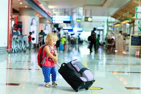 klein meisje met een koffer reizen in de luchthaven, kinderen reizen