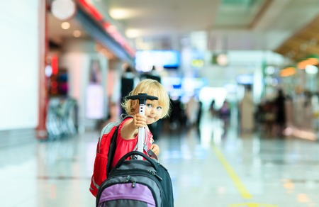 cute blonde: little girl with suitcase travel in the airport, kids travel