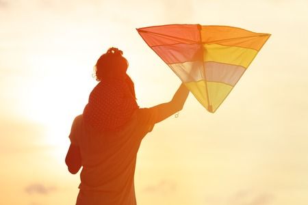 flying kite: father and little daughter having fun flying kite at sunset Stock Photo
