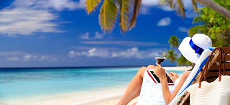 panoramic photo of woman drinking wine and looking at touch pad on tropical beach 스톡 콘텐츠
