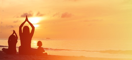 silhouette of mother and kids doing yoga at sunset, panorama