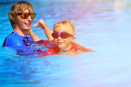 Padre enseñando a su pequeño hijo a nadar, deporte niños