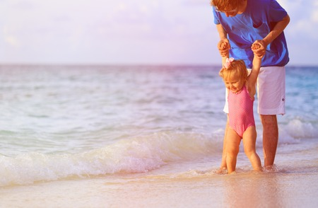 apoyo familiar: father and little daughter walking on summer beach