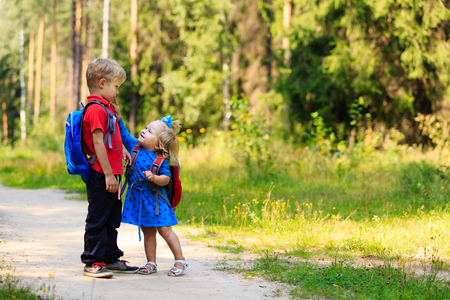 infant school: happy little boy and girl with backpacks in summer, kids go to school