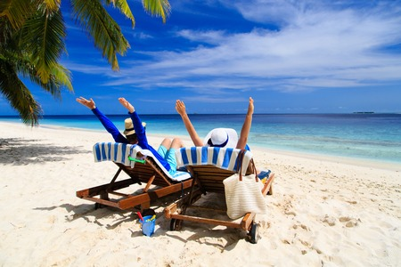 holiday destination: happy couple relax on a tropical sand beach
