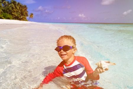 little boy swimming: little boy swimming holding shell on tropical beach Stock Photo