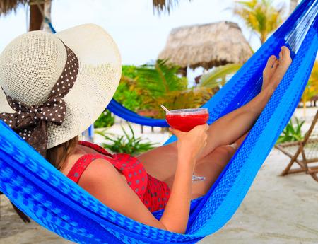 hamaca: Mujer con el coctel se relaj� en la hamaca en la playa tropical