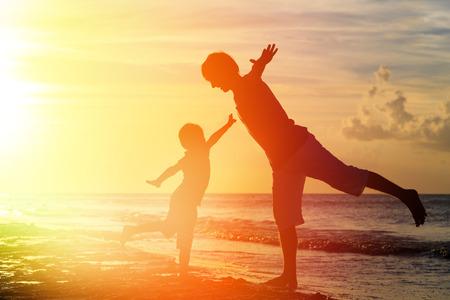 silueta humana: padre e hijo se divierten en la playa de la puesta del sol
