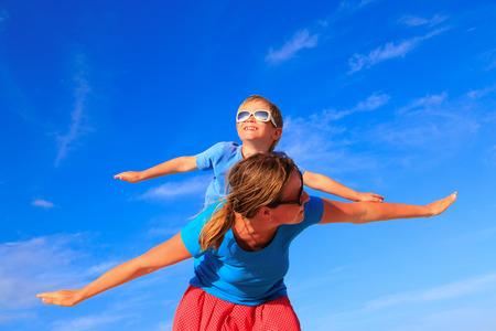 familias felices: Madre y pequeño hijo que juega el aeroplano en el cielo azul del verano