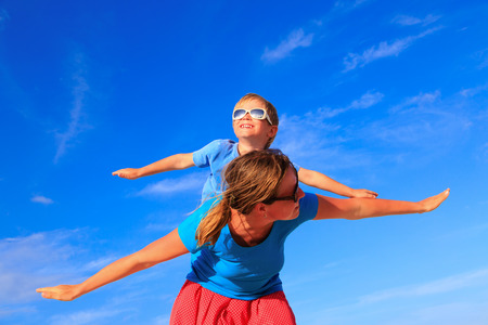 happy families: Mother and little son playing airplane on blue summer sky