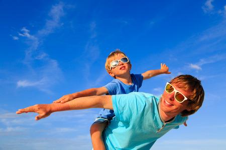 familias felices: Padre y pequeño hijo jugando en el cielo azul del verano