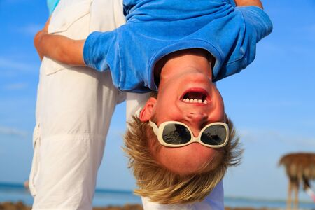 child laughing: little boy having fun with dad on summer beach