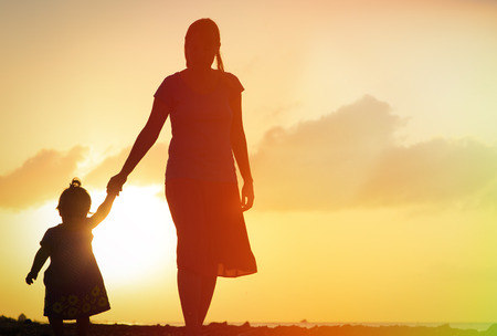 woman sunset: mother and little daughter walking on sand beach at sunset