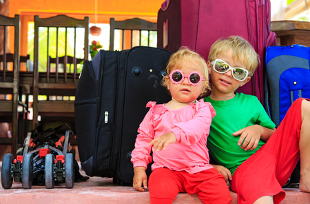 femme avec valise: kids travel concept- little boy and toddler girl sitting on suitcases ready to travel