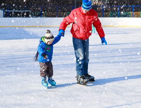father and little son learning to skate in winter snow Foto de archivo