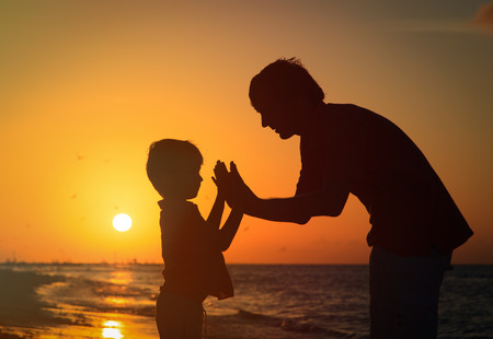 father and son playing at sunset sea
